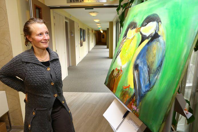 Tessa bij een van haar schilderijen. Haar doeken laten dingen uit de natuur zien, zoals koolmezen of landschappen.