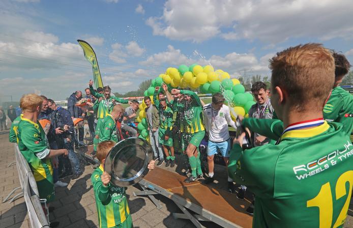 FC Binnenmaas viert het kampioenschap met champagne.