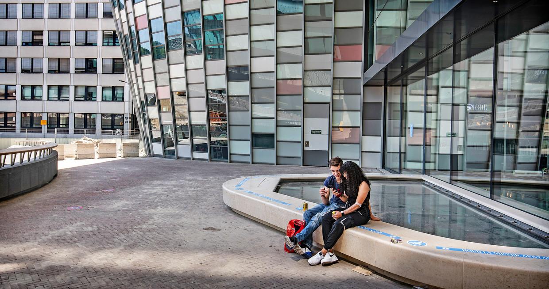 Een jong stelletje communiceert via een smartphone op een futuristische plek bij Hoogcatharijne. Beeld Guus Dubbelman / de Volkskrant
