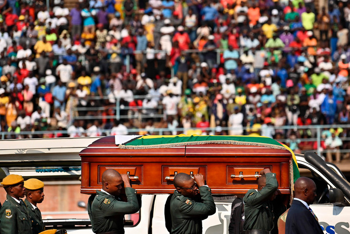 De kist met daarin het lichaam van Mugabe wordt het stadion ingedragen.
