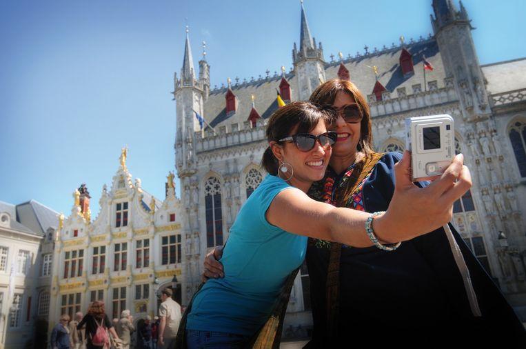 Toeristen nemen een selfie in Brugge.