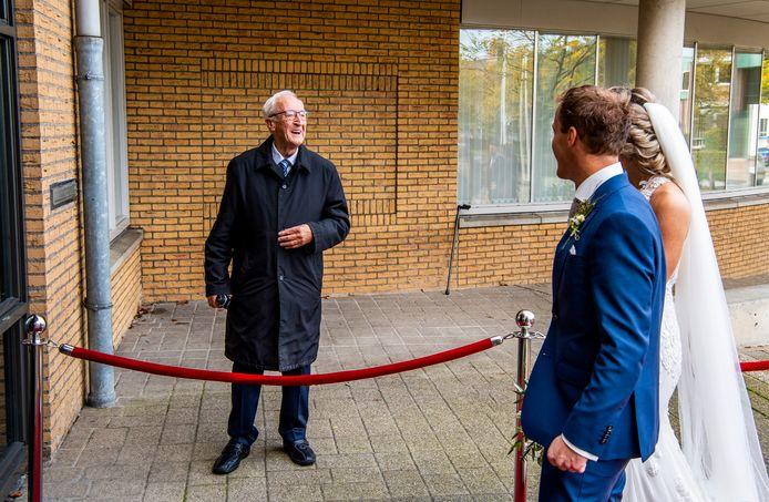 Zo trots als een pauw: opa Henk van Veen - gewapend met fotocamera - zwaait naar zijn kleinzoon Jordy en diens vrouw Anne Lotte terwijl ze naar het gemeentehuis van Hardinxveld-Giessendam lopen.