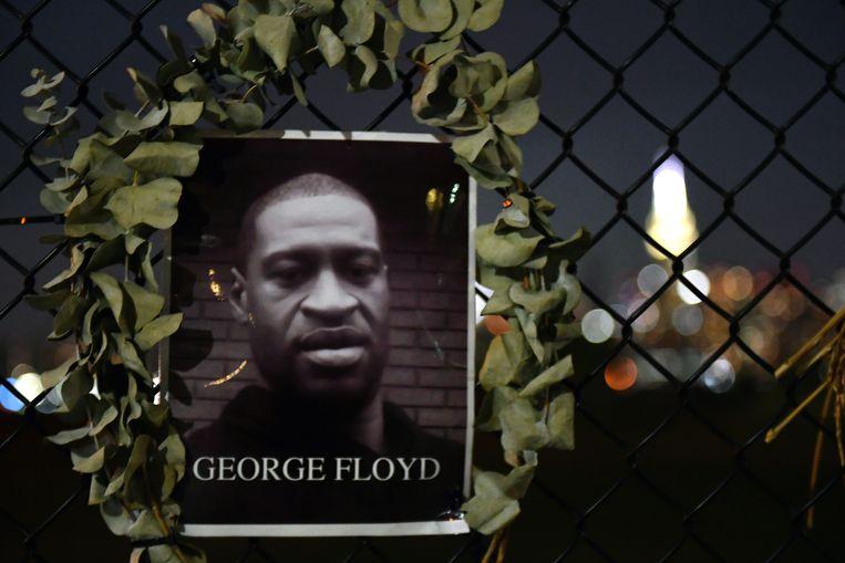 Een foto van George Floyd is opgehangen aan een hek in New York.  Beeld AFP