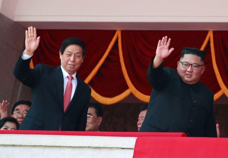 Kim Jong-Un en Li Zhansu zwaaien naar het publiek tijdens de parade. Beeld ANP