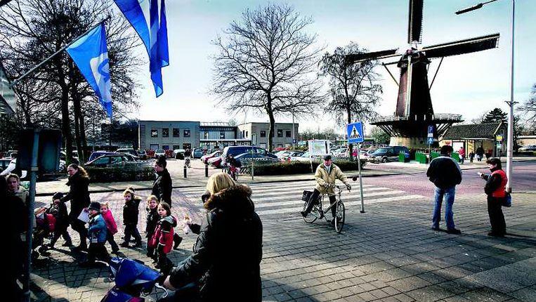 Molen de Hoop is in Rozenburg een symbool van vervlogen tijden, het gemeentehuis ernaast is dat niet. (FOTO WERRY CRONE, TROUW) Beeld