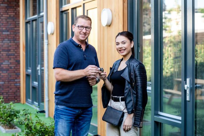 Wiljan Huijben van WonenBreburg overhandigt de sleutels aan Elvira van Welzenes voor haar nieuwe woning.