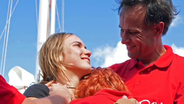 Laura Dekker omhelst haar zusje Kim (13). Rechts haar vader.