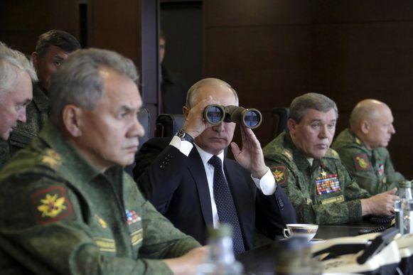 Russisch president Vladimir Poetin en zijn minister van Defensie (links op de foto) op de eerste rij tijdens militaire oefeningen in september.