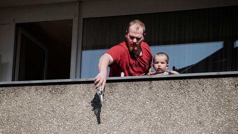 Een bewoner schudt de laatste druppels uit zijn bierflesje op een balkon in de wijk Nordstadt in Dortmund. Beeld Daniel Rosenthal / de Volkskrant