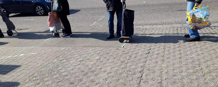 Een rij wachtenden voor de Voedselbank in Hatert. Met stoepkrijt is geprobeerd de anderhalve meter corona-afstand zichtbaar te maken.