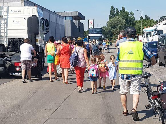 Reizigers stappen richting de bus.