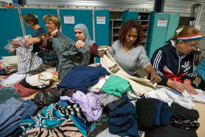 Janneke van Dijk, Josée Stienstra, Hala Albunni, Katou Youlla en Nadie Khalifa sorteren tweedehand kleding voor minima in Overbetuwe.