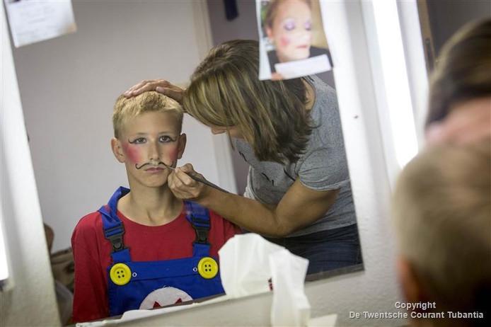 Ouders van de Drie-eenheid helpen een handje mee bij het schminken van hun kinderen voor de afscheidsmusical.