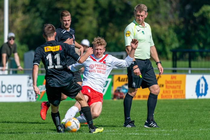 Rick Beijer van RKSV Driel in duel met Max Roelofs (11) van Jonge Kracht. De Huissenaren wonnen verrassend ruim: 0-6.