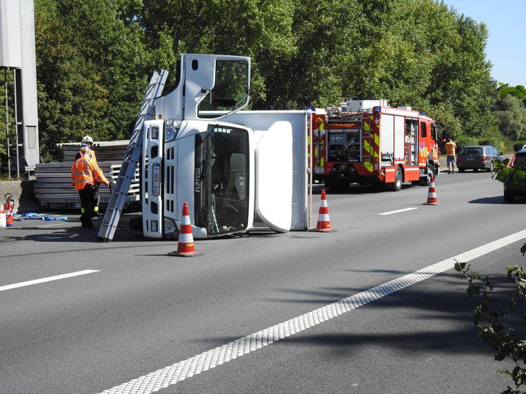 De bestelwagen en de aanhangwagen, gevuld met stellingen, lag op zijn zijkant op de autosnelweg.