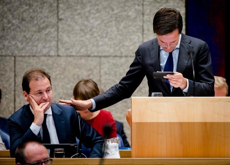 Premier Mark Rutte wordt via de mobiele telefoon van minister Asscher geholpen met statistieken. Beeld ANP