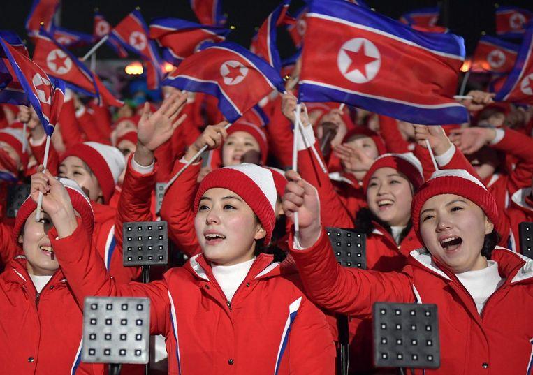 Noord-Koreaanse cheerleaders, die door Pyongyang naar Zuid-Korea zijn gestuurd, zwaaien met de Noord-Koreaanse vlag vlak voor de openingsceremonie. Beeld AFP