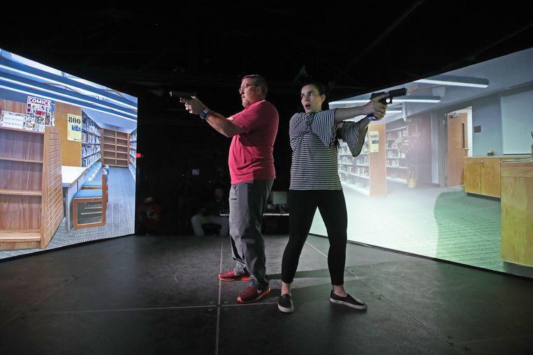 Leraren in de Amerikaanse staat Utah doen een vuurwapentraining met behulp van een videosimulator. Zo hopen zij voorbereid te zijn op een dreigende of echte schietpartij in hun school.  Beeld AFP