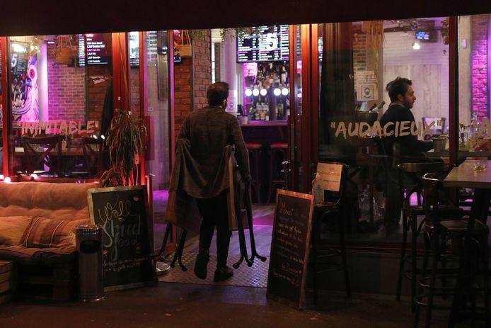 Een werknemer van een restaurant in Parijs tijdens het opruimen van enkele terrastafels maandag. Momenteel moeten horecazaken er nog vroeger de deuren sluiten.