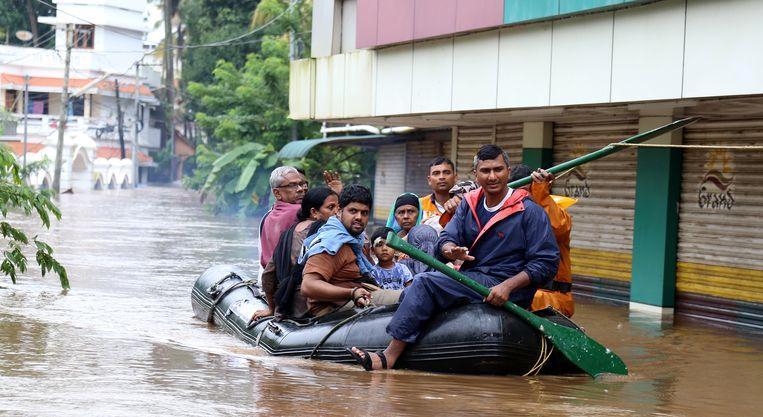 Mensen proberen zich in een rubberboot in veiligheid te brengen in de plaats Kochi in de provincie Kerala. Beeld EPA
