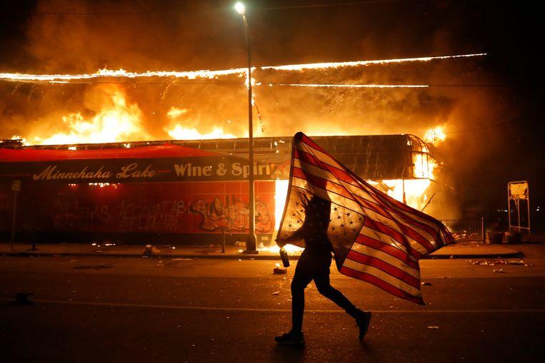 Een betoger met een ondersteboven Amerikaanse vlag. Beeld AP
