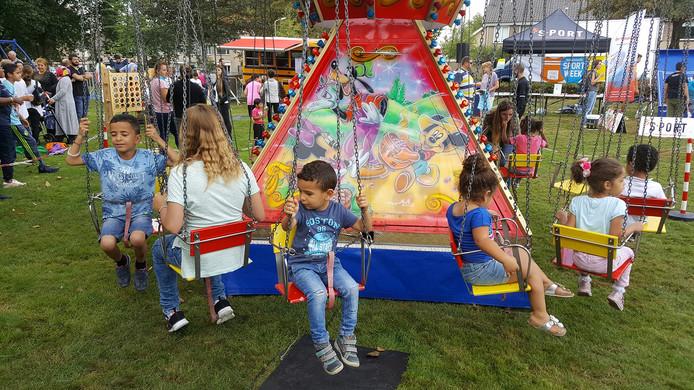 Kinderen hebben het naar hun zin in de schommels op het buurtfeest op de Kruiskmap in Den Bosch.
