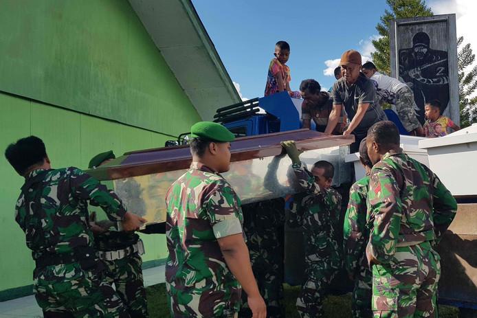 Indonesische soldaten voeren kisten aan voor de lichamen van de omgekomen bouwvakkers.