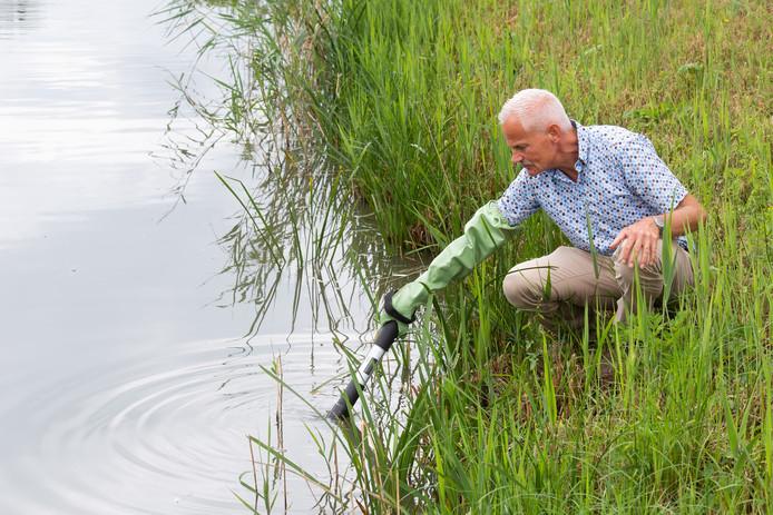 Martin Stamhuis van waterschap Brabantse Delta meet het water in de Bredase Huifakkerstraat.