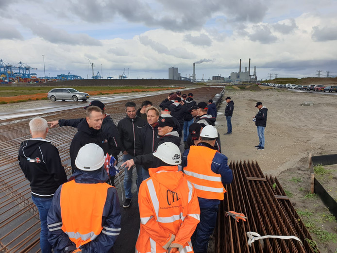 Havenwerkers kijken bij de aanleg van de interne baan voor containers. In het midden (tweede van links) staat Niek Stam