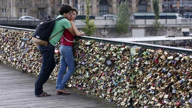 De Op de Pont des Arts in Parijs verzegelen verliefde stelletjes hun liefde. Beeld afp