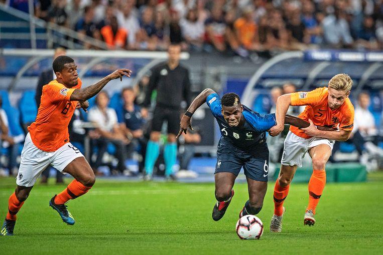Paul Pogba is te sterk voor Frenkie de jong, zoals Frankrijk te sterk is voor Nederland. Georginio Wijnaldum snelt te hulp. Beeld null