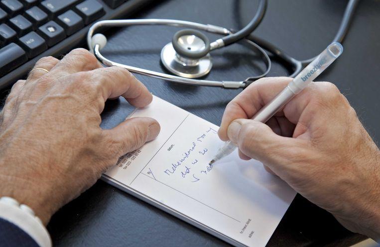 Deze huisarts schrijft een patiënt een doktersbriefje voor.