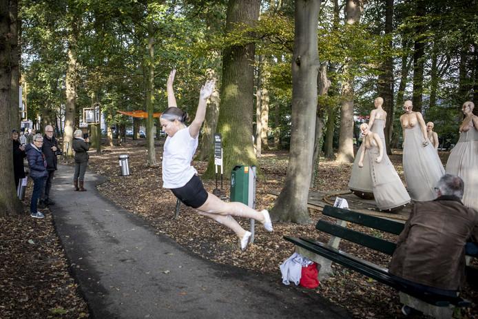 Dansers van InnerAll trekken bekijks bij het kunstwerk Witte Wieven in het Eeshofbos.