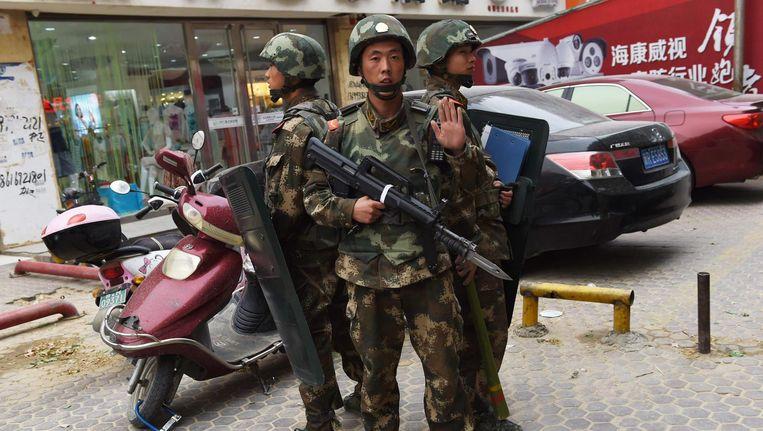 Politieagenten bij een winkelcentrum in Hotan in Xinjiang in 2015. Beeld AFP