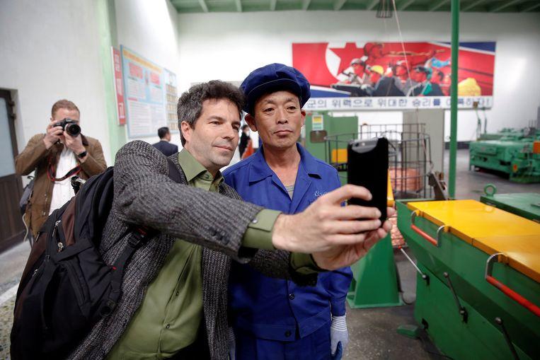 Een buitenlandse journalist maakt een selfie met een Noord-Koreaanse arbeider tijdens een tour die tijdens de congresdagen is georganiseerd door de overheid. Beeld reuters