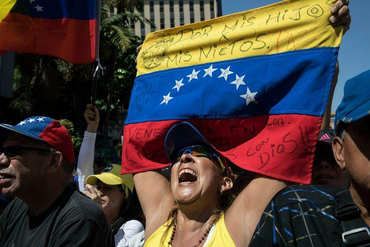 Demonstrante met de Venezolaanse vlag bij een antiregeringsdemonstratie, zaterdag in Caracas. 'Voor mijn kinderen en voor mijn kleinkinderen', staat op de vlag geschreven. Beeld AP