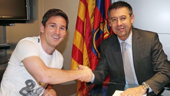 Lionel Messi met Barcelona-voorzitter Josep Maria Bartomeu, bij het ondertekenen van een nieuwe verbintenis.