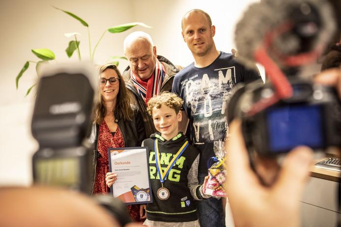 """Sem Groot Rouwen (11), samen met zijn vader, moeder en opa nadat hij het eerste kinderlintje van Oldezaal ontving: """"Ik, een held? Eh, ja!"""""""
