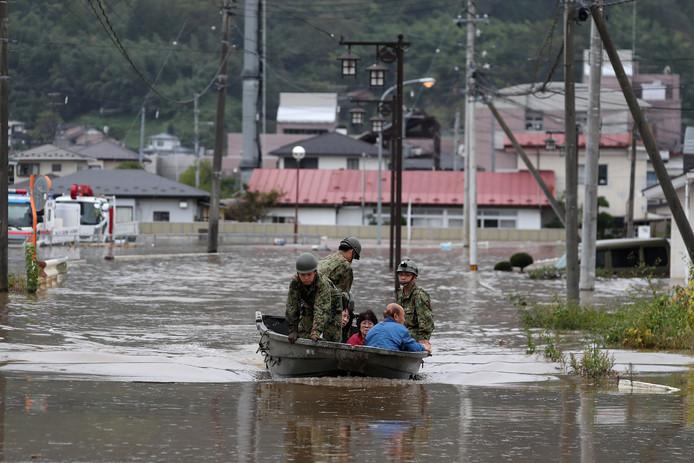 Reddingswerkers halen bewoners uit hun overstroomde huizen.