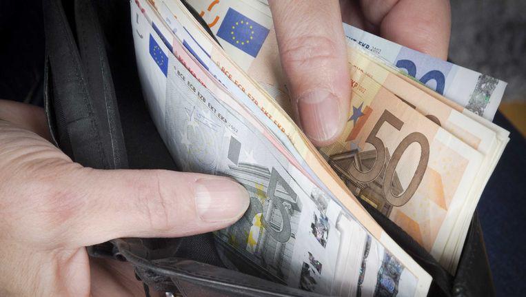 Een man haalt geld uit zijn portemonnee. Beeld null