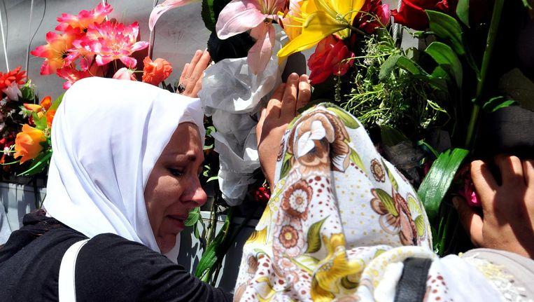 Bosnische vrouwen raken de grafkisten aan van nieuw geindentificeerde lichamen op 9 juli in Sarajevo Beeld afp