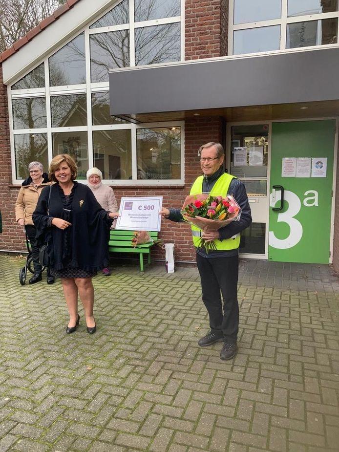 Wethouder Laura Matthijssen reikt de cheque en bloemen uit aan Wim Pijlman, een van de wandelcoordinatoren van de Wandelchallenge.