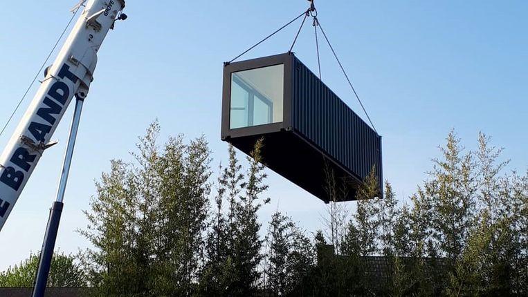 Met een kraan wordt de container in de tuin geplaatst.