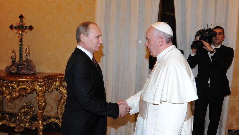 De Russische president Poetin schudt de hand van paus Franciscus. Beeld EPA