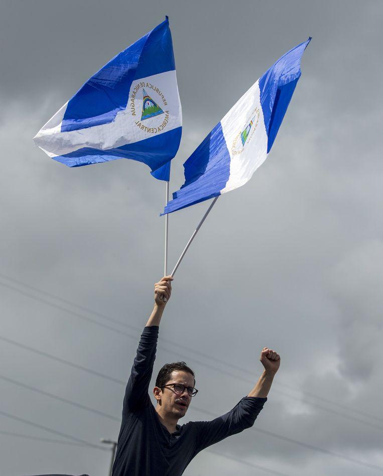 Een burger houdt twee vlaggen van Nicaragua omhoog.