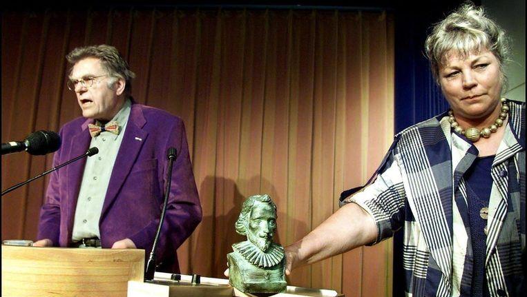 Gerrit Krol bij de uitreiking van de P.C. Hooft-prijs in 2001. Zijn echtgenote toont het beeldje aan de aanwezige pers. Beeld anp