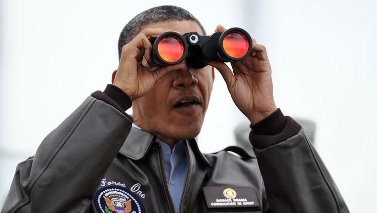 De Amerikaanse president Obama kijkt door een verrekijker. Beeld afp