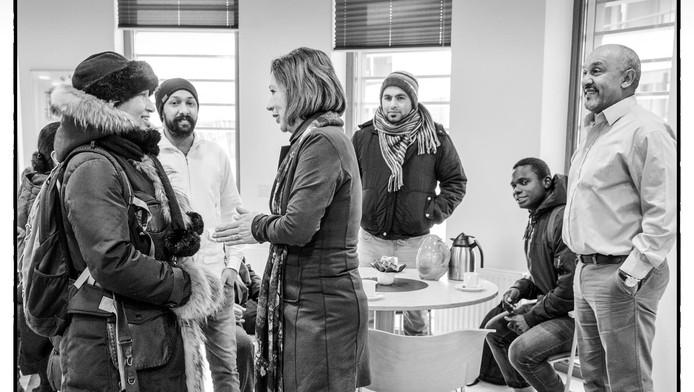 Wethouder Giny Luth maakt een praatje met asielzoekers in de bibliotheek in Ter Apel, waar meet-and-greets worden georganiseerd.