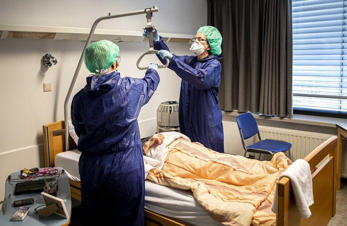 Medewerkers geven zorg aan een coronapatiënt op een speciale afdeling in het Amphia ziekenhuis in Breda voor ouderen.
