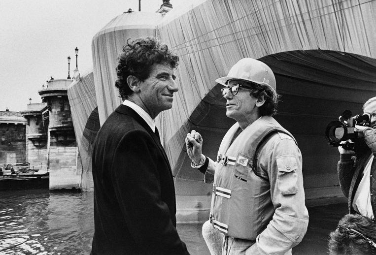 1985: De Franse minister van cultuur Jack Lang (L) praat met Christo tijdens het inpakken van de Pont Neuf. Beeld AFP